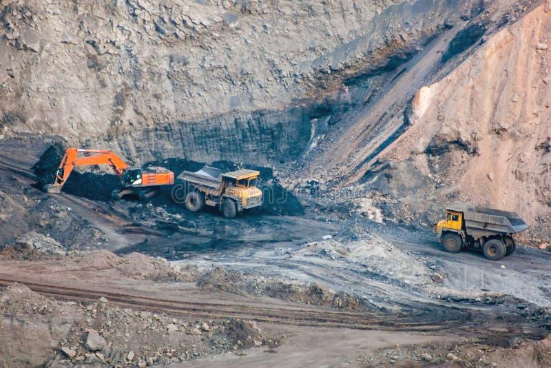 Crawler excavator and dump trucks in a quarry stock photo