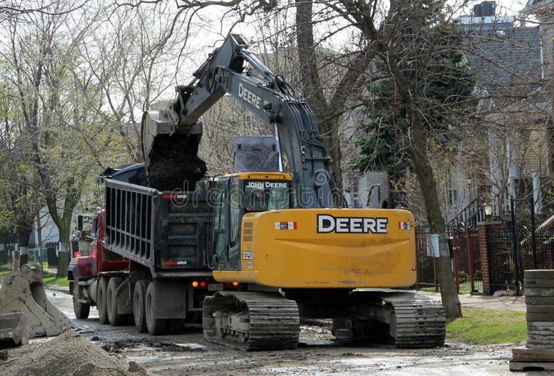 A crawler excavator loads dirt onto a dump truck in Chicago stock photography
