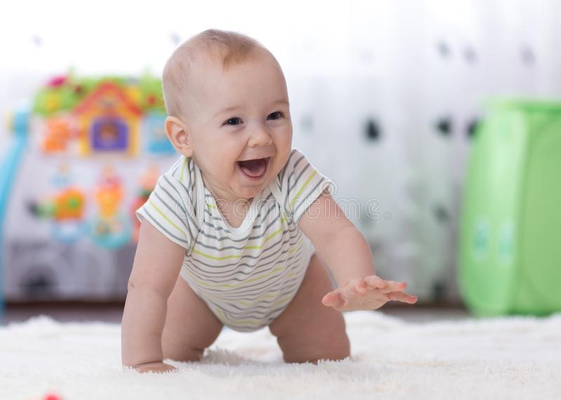 Crawling funny baby boy indoors at home. Crawling funny baby boy in nursery at home royalty free stock photo