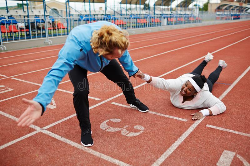Crawling to finish. Young exhausted plus-sized women in activewear talking to trainer pulling her towards finish line royalty free stock image