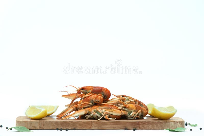 Crayfish decorated with lemon and spices on a white background. Crayfish on a wooden board stock images