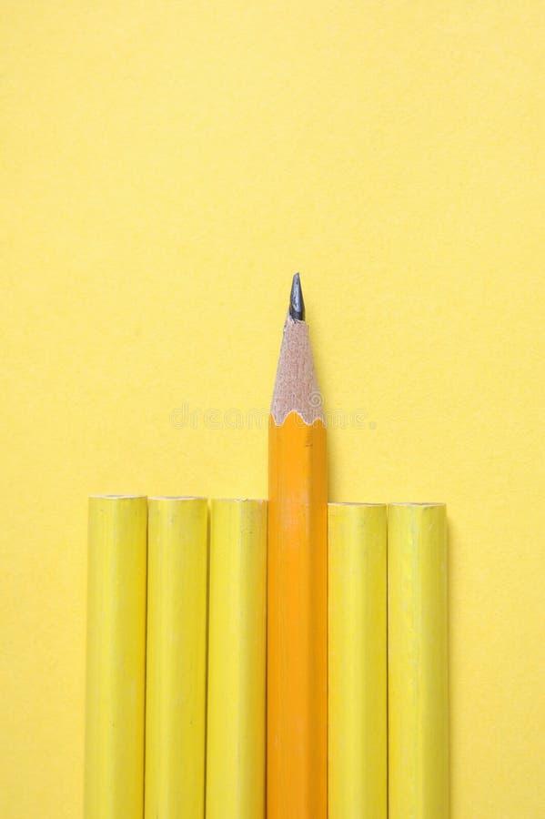 Crayon affilé sur le fond jaune image stock
