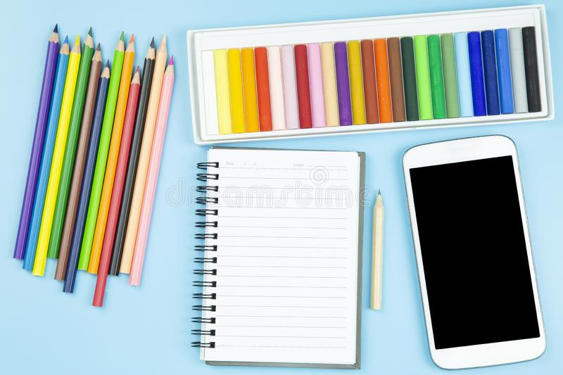 Crayon and book mobile phone topview flatlay on blue background. Pastel style stock photo