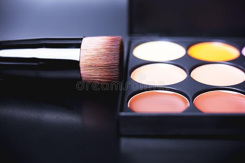 Crayon correcteur et correcteurs de palette Base de maquillage sur le fond noir images stock