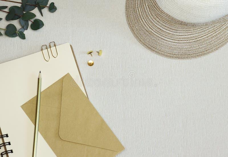 Crayon d'or, trombones, goupilles, enveloppe sur le carnet ouvert photographie stock