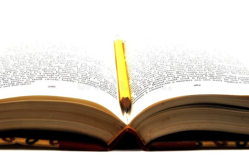 Crayon dans un livre photos stock