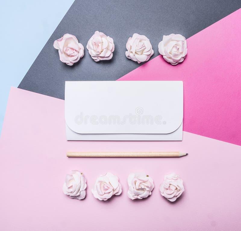 Crayon de fond d'enveloppe blanche et papier multicolores avec les roses roses, carte de voeux pour des clo de vue supérieure de  photo libre de droits