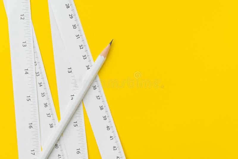 Crayon et bandes de mesure blanches de centimètre et pouces sur le fond jaune vif, la longueur, instrument et outils le longs ou  photos libres de droits