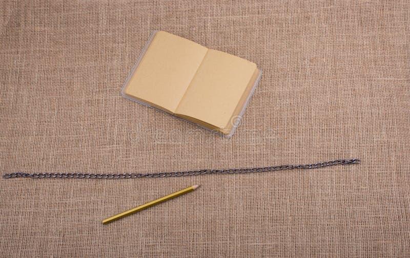 Crayon et carnet avec une chaîne au milieu images libres de droits