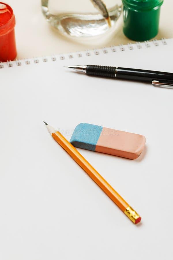 Crayon et gomme sur une page de papier blanche, verticale images libres de droits