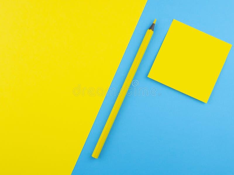 Crayon jaune en bois d'isolement sur le papier et le cartel bleus de texture avec la place jaune Calibre minimaliste avec l'espac images libres de droits