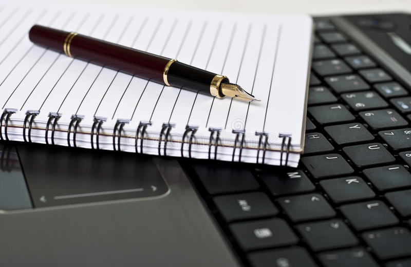 Crayon lecteur, bloc-notes et ordinateur portatif sur le bureau photos libres de droits