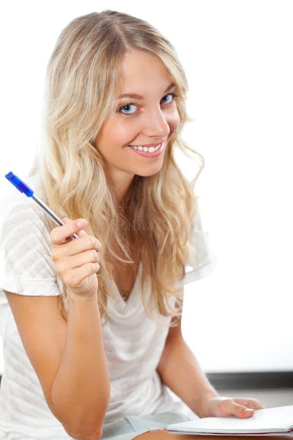 Crayon lecteur et bloc-notes de fixation blonds de femme image libre de droits