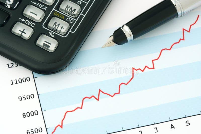 Crayon lecteur et calculatrice sur le graphique positif de revenu images libres de droits