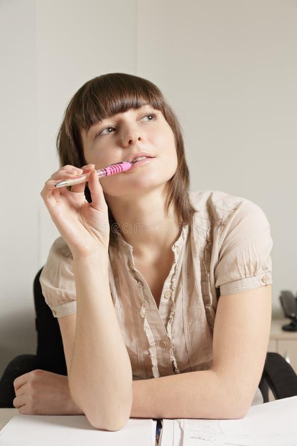 Crayon lecteur mordant de jeune femme songeur images stock