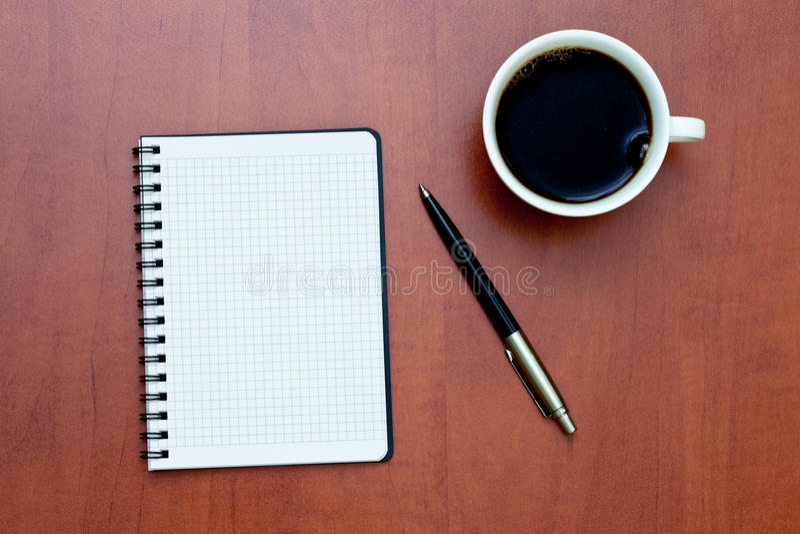Crayon lecteur sur un carnet de notes à spirale blanc avec la cuvette de café image stock