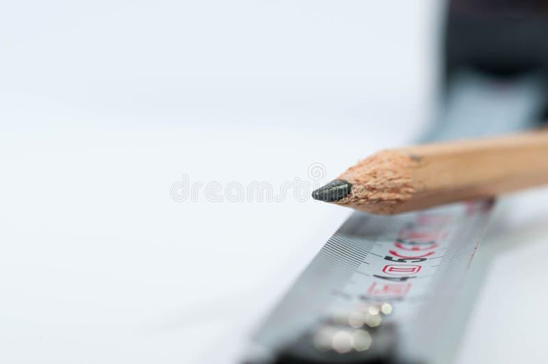 Crayon pointu sur la mesureuse de bande sur le blanc images stock