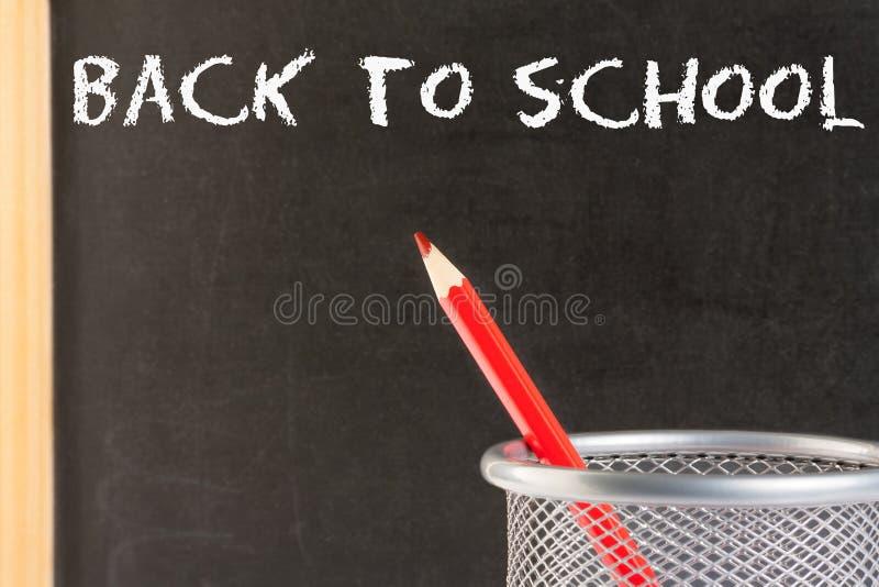 Crayon rouge dans le récipient contre le tableau noir photographie stock