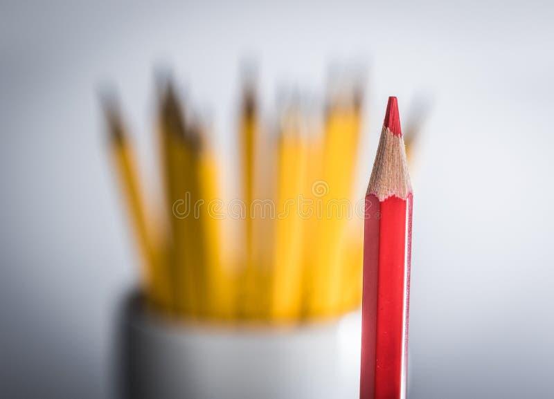 Crayon rouge solitaire contre un groupe de crayons jaunes image stock
