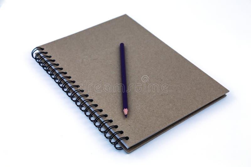 Crayon sur le carnet vérifié d'isolement photographie stock