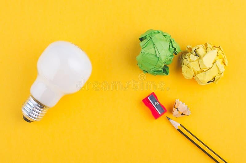 Crayonnez, chiffonnez le papier et l'ampoule au-dessus du fond jaune photographie stock libre de droits