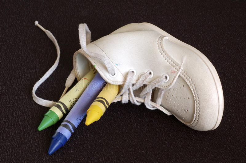 Crayons In Baby Shoe. Closeup shot of crayons in a baby shoe stock image