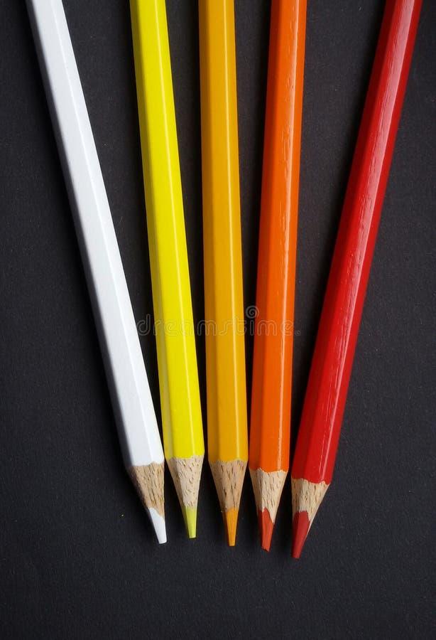 Crayons colorés au-dessus de fond noir Couleurs chaudes Blanc, jaune, orange et rouge images stock
