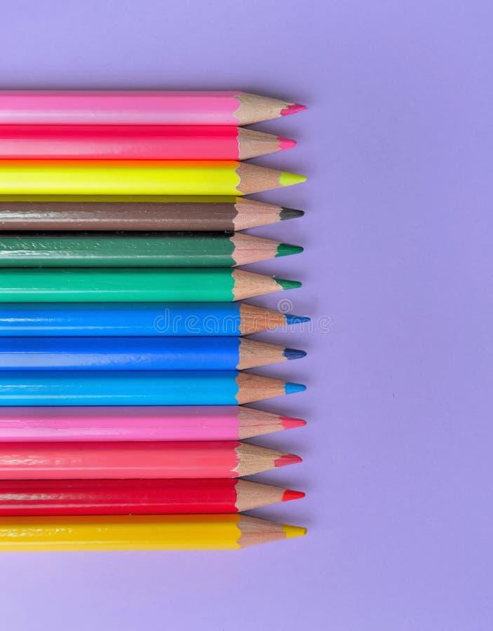 crayons colorés dans la ligne sur le fond mauve photos libres de droits