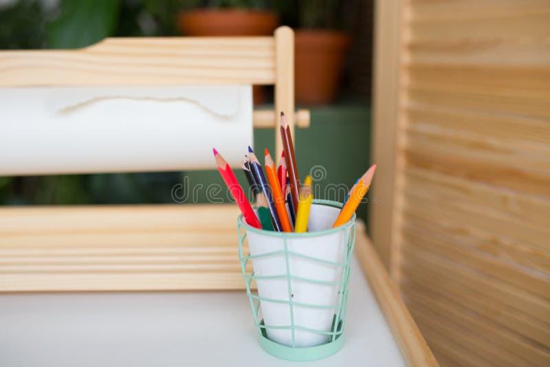 Crayons colorés dans une glace créativité du ` s d'enfants, objets pour la conception crayons lumineux sur la lumière de table photographie stock