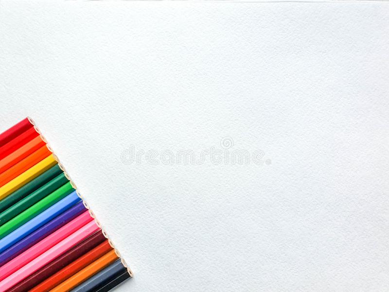 Crayons colorés en bois, style d'arc-en-ciel, sur la feuille blanche de papier de dessin avec la texture spécifique Copiez l'espa image stock