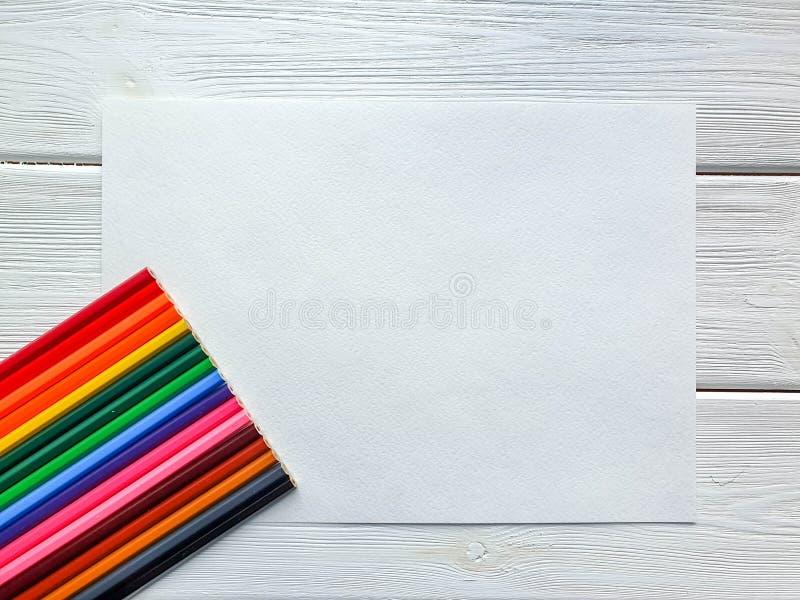 Crayons colorés en bois, style d'arc-en-ciel, sur la feuille de papier de dessin avec la texture spécifique, et le fond en bois b images stock