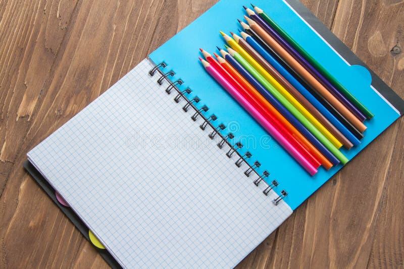 Crayons colorés et bloc-notes ouvert sur le fond en bois photographie stock
