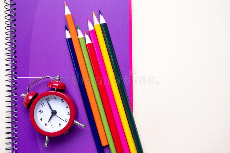 Crayons colorés et carnets pourpres et un réveil rouge Fournitures de bureau d'?cole et photo libre de droits