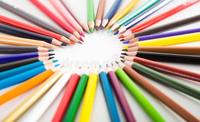 Crayons colorés se trouvant autour du coeur photographie stock