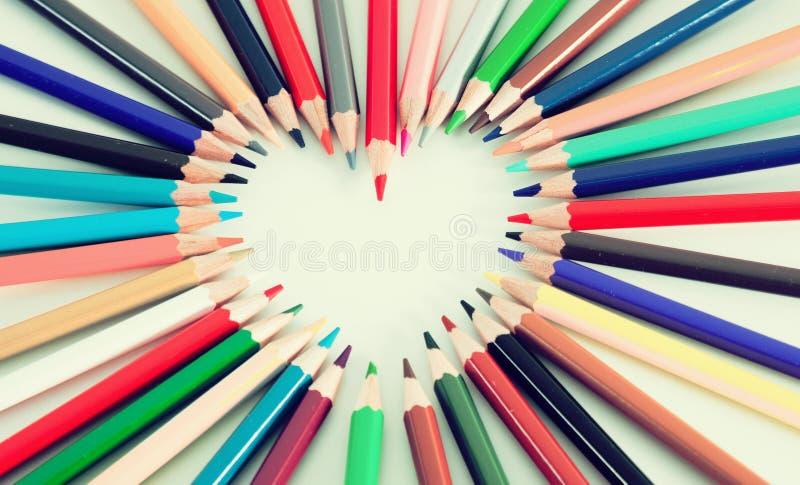 Crayons colorés se trouvant autour du coeur photo stock