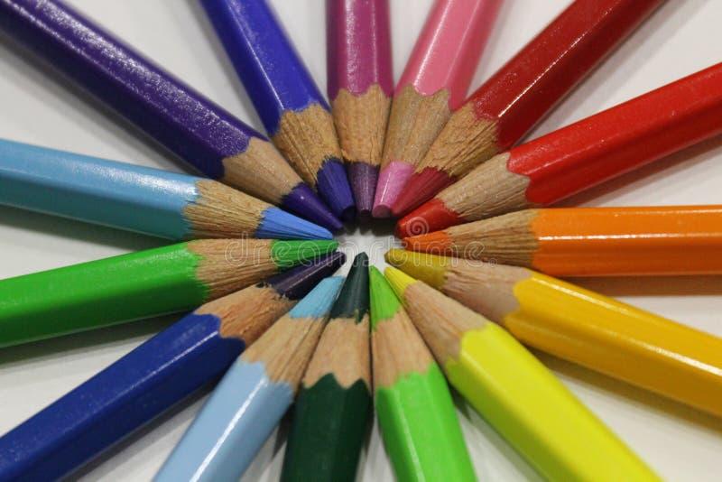 Crayons colorés se trouvant autour du coeur sur un fond blanc photo stock