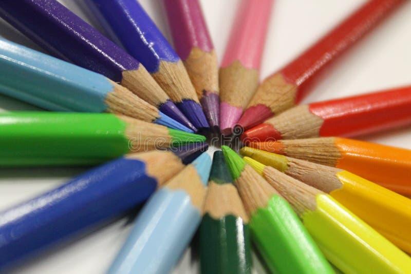 Crayons colorés se trouvant autour du coeur sur un fond blanc images libres de droits