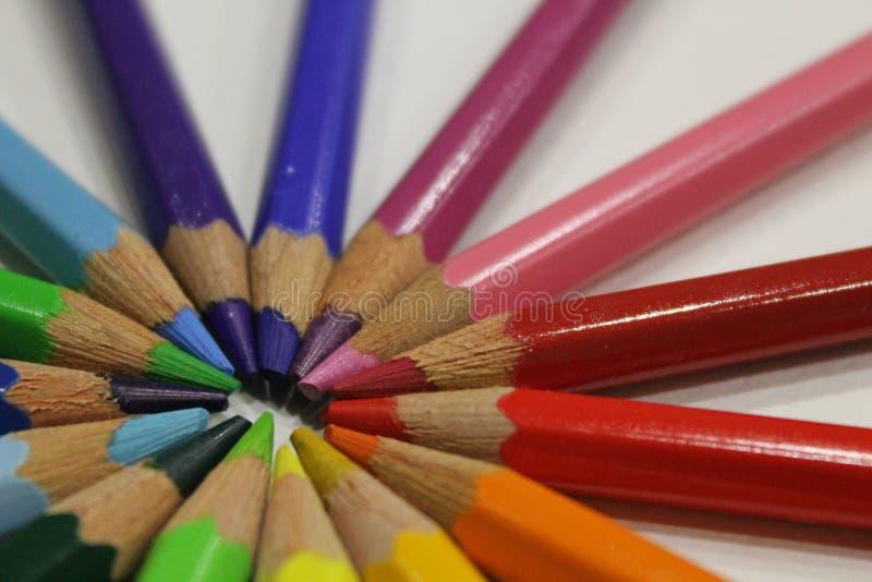 Crayons colorés se trouvant autour du coeur sur un fond blanc image libre de droits