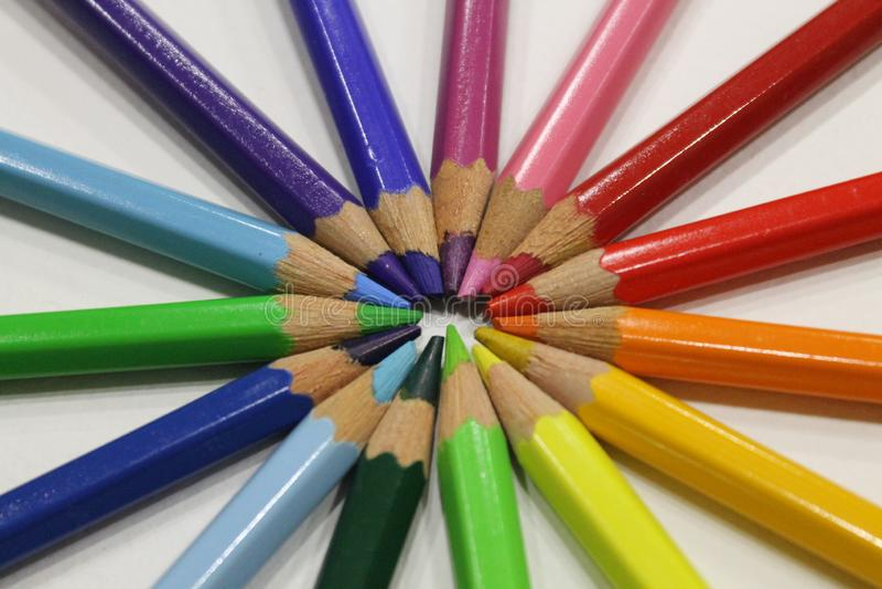 Crayons colorés se trouvant autour du coeur sur un fond blanc images stock