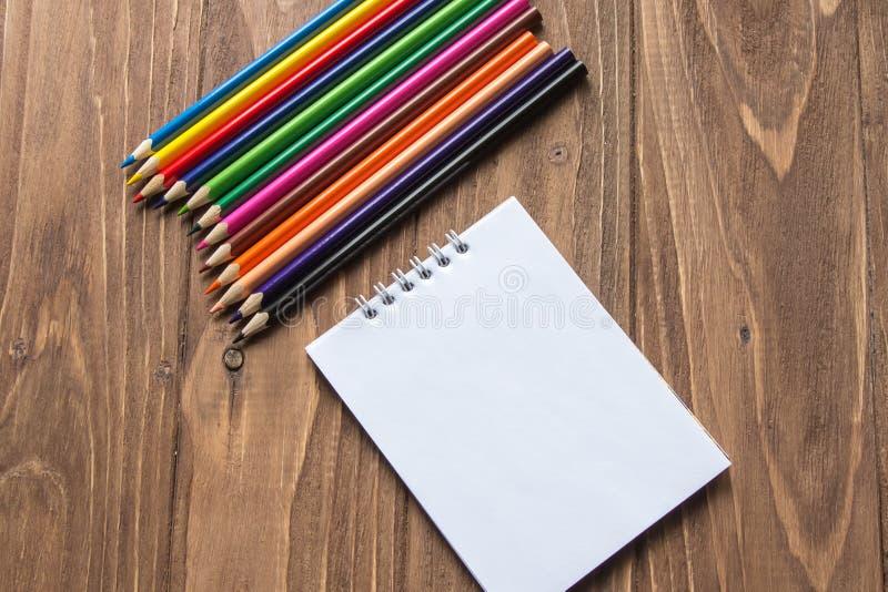 Crayons colorés sur le dessus et bloc-notes sur le fond en bois photo libre de droits