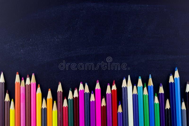 Crayons colorés sur le fond noir photo stock
