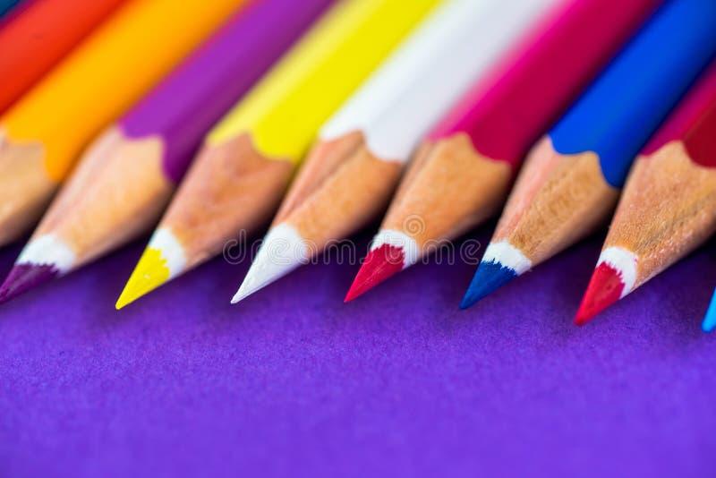 Crayons colorés sur un fond violet avec l'espace pour le texte images stock