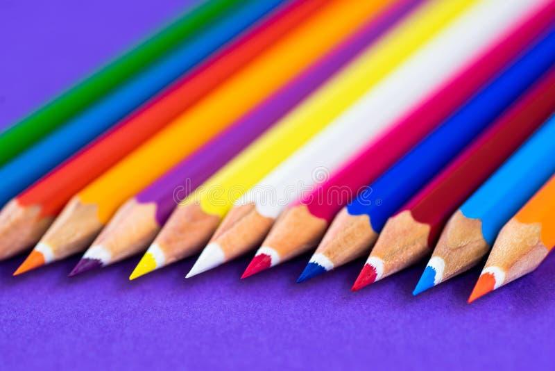 Crayons colorés sur un fond violet avec l'espace pour le texte photos libres de droits