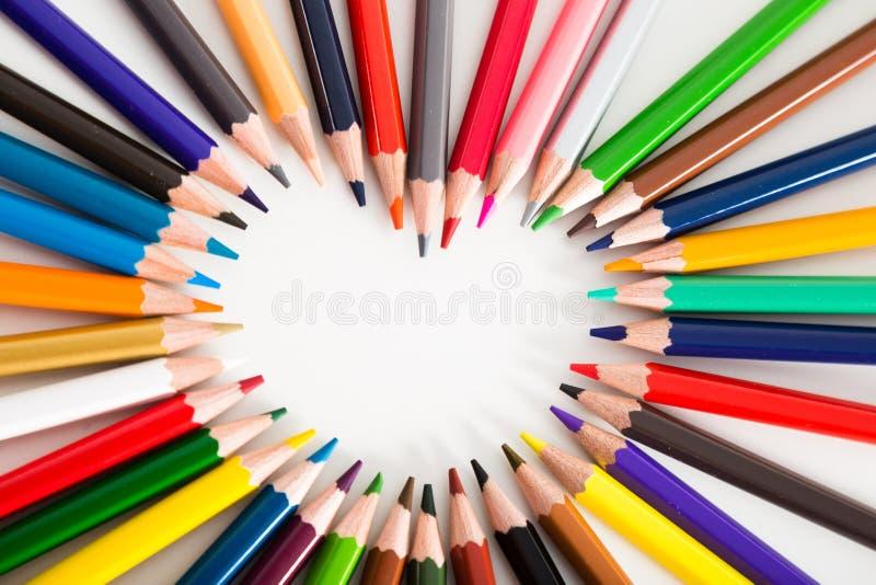 Crayons color?s se trouvant autour du coeur photographie stock