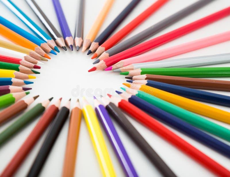 Crayons color?s se trouvant autour du coeur photo stock