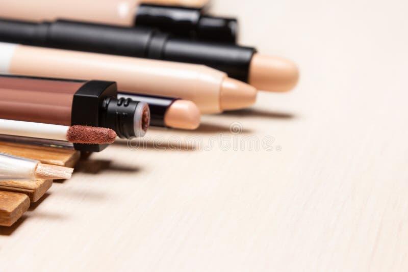Crayons correcteurs et base de maquillage dans une rangée sur la table en bois blanche photo libre de droits