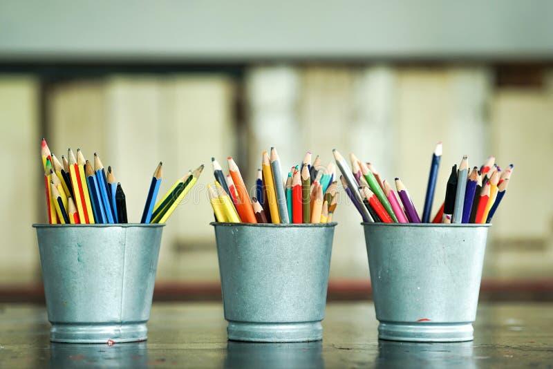 Crayons de couleur émoussés par plan rapproché dans des seaux en métal image stock
