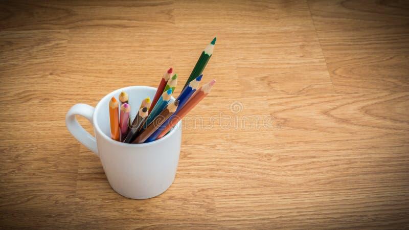 Crayons de couleur dans la tasse de café blanc image libre de droits