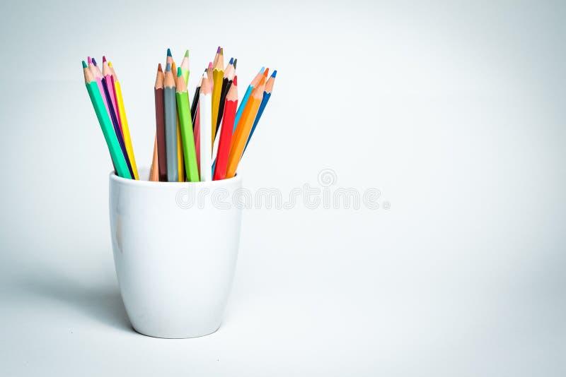 Crayons de couleur dans une tasse blanche photographie stock libre de droits