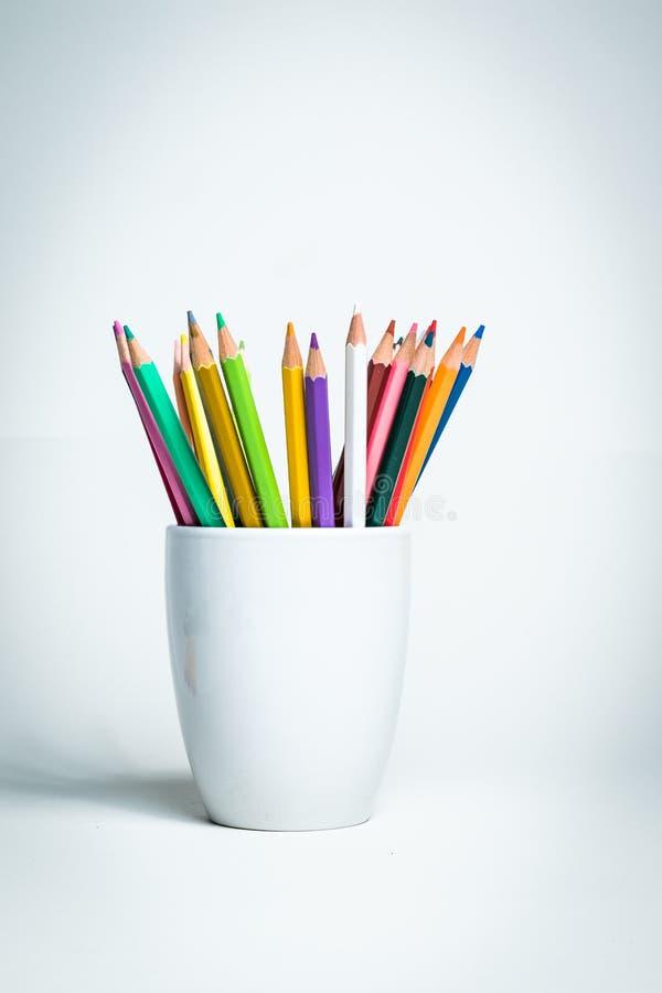 Crayons de couleur dans une tasse blanche photographie stock